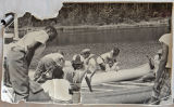 [Men, women and children boarding canoes on a lake]