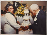 [Man and woman cutting a 50th anniversary cake]