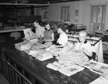 [Vick Chemical employees going through newspapers]