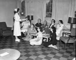 [A nurse talking to a group of women at polio hospital]