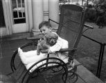 [Boy in wheelchair with dog]