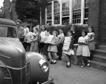 [Youth carrying boxes outside old Peck School building for American Red Cross activity]