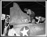 [Phyllis Snyder and other Women Marines working on airplane tail repair, circa 1943]