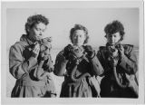 [Three WACs prepare for gas mask drill, 1943]
