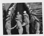 [Officers distribute awards on ship, circa 1946.]