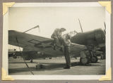 [Two WAVES members, one sitting on wing of an SNJ aircraft, Naval Air Station Anacostia, D.C.,...
