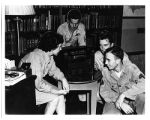 [WAC and male soldiers around radio, circa 1944]