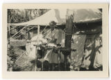 [Daphine Doster Mastroianni washing at basin outside of tent, India, 1945.]