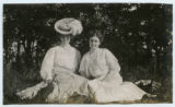 [Two women seated in the grass]