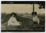 [Two women seated outdoors]