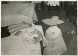 [Student and Garments on Bed, 1956]