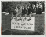 [Students Sitting on UNCG Entrance Sign]